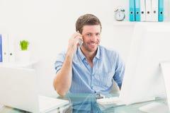 Χαμογελώντας επιχειρηματίας στο τηλέφωνο στο γραφείο Στοκ Φωτογραφία