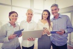 Χαμογελώντας επιχειρηματίες με τις ηλεκτρονικές συσκευές Στοκ φωτογραφία με δικαίωμα ελεύθερης χρήσης
