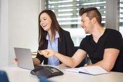 Χαμογελώντας επιχειρηματίες με το lap-top που επικοινωνούν στο γραφείο Στοκ Εικόνες