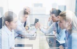 Χαμογελώντας επιχειρηματίες που έχουν τη σύγκρουση στην αρχή Στοκ φωτογραφία με δικαίωμα ελεύθερης χρήσης