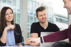 Χαμογελώντας επιχειρηματίες που εξετάζουν την εξήγηση συναδέλφων στο γραφείο Στοκ Φωτογραφία