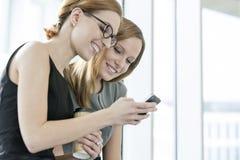 Χαμογελώντας επιχειρηματίες που χρησιμοποιούν το τηλέφωνο κυττάρων κατά τη διάρκεια του σπασίματος στην αρχή Στοκ Φωτογραφίες