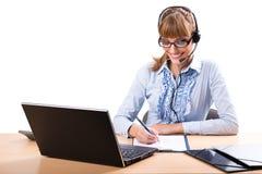 Χαμογελώντας επιχειρησιακή γυναίκα με το ακουστικό στην αρχή Στοκ Φωτογραφία
