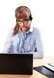 Χαμογελώντας επιχειρησιακή γυναίκα με το ακουστικό στο γραφείο ι Στοκ Φωτογραφία