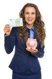 Χαμογελώντας επιχειρησιακή γυναίκα που παρουσιάζει εκατό ευρώ και piggy τράπεζα Στοκ εικόνα με δικαίωμα ελεύθερης χρήσης