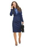 Χαμογελώντας επιχειρησιακή γυναίκα που πηγαίνουν κατ' ευθείαν και ομιλούν κινητό τηλέφωνο Στοκ φωτογραφία με δικαίωμα ελεύθερης χρήσης