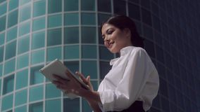 Χαμογελώντας επιχειρησιακή γυναίκα που στέκεται υπαίθρια μια ηλιόλουστη ημέρα και που εργάζεται στην ταμπλέτα της φιλμ μικρού μήκους