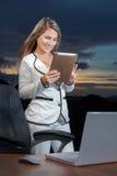 Χαμογελώντας επιχειρησιακή γυναίκα που χρησιμοποιεί την ψηφιακή ταμπλέτα στο γραφείο Στοκ Εικόνες