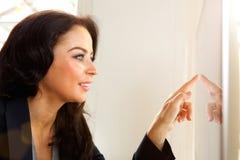 Χαμογελώντας επιχειρησιακή γυναίκα σχετικά με τη οθόνη υπολογιστή Στοκ Φωτογραφία