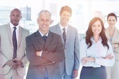 Χαμογελώντας επιχειρησιακή ομάδα που στέκεται μπροστά από ένα φωτεινό παράθυρο στοκ εικόνες
