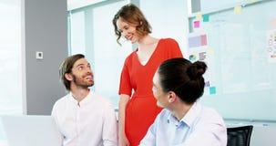 Χαμογελώντας επιχειρησιακοί συνάδελφοι που συζητούν πέρα από το lap-top στη αίθουσα συνδιαλέξεων φιλμ μικρού μήκους