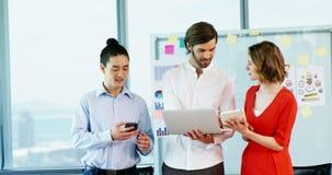 Χαμογελώντας επιχειρησιακοί συνάδελφοι που χρησιμοποιούν το κινητό τηλέφωνο, την ψηφιακά ταμπλέτα και το lap-top απόθεμα βίντεο