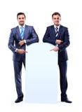 Χαμογελώντας επιχειρησιακό δύο άτομο που παρουσιάζει κενή πινακίδα στοκ φωτογραφία