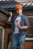 Χαμογελώντας εργάτης οικοδομών για τη σκάλα βημάτων κάτω από τη στέγη σπιτιών Στοκ φωτογραφίες με δικαίωμα ελεύθερης χρήσης