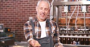 Χαμογελώντας εργαζόμενος ζυθοποιείων που εξηγεί τους διαφορετικούς σπόρους απόθεμα βίντεο