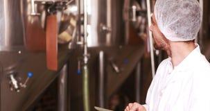 Χαμογελώντας εργαζόμενος ζυθοποιείων που χρησιμοποιεί την ταμπλέτα απόθεμα βίντεο