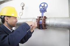 Χαμογελώντας εργαζόμενος που ελέγχει τον εξοπλισμό πετρελαιαγωγών σε εγκαταστάσεις αερίου, Πεκίνο, Κίνα στοκ εικόνα