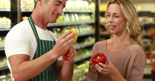 Χαμογελώντας εργαζόμενος που συμβουλεύει τον όμορφο πελάτη φιλμ μικρού μήκους
