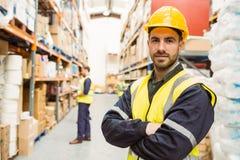 Χαμογελώντας εργαζόμενος που φορά την κίτρινη φανέλλα με τα όπλα που διασχίζονται Στοκ φωτογραφία με δικαίωμα ελεύθερης χρήσης