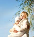 Χαμογελώντας ευτυχές ξανθό αγκάλιασμα γυναικών και κοριτσιών υπαίθριο στο πάρκο ενάντια στο μπλε ουρανό Στοκ φωτογραφία με δικαίωμα ελεύθερης χρήσης