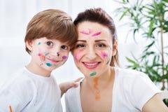 Χαμογελώντας ευτυχής λατρευτή οικογένεια με τα χρώματα σε τους πρόσωπο - αστείο μ Στοκ εικόνες με δικαίωμα ελεύθερης χρήσης