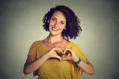 Χαμογελώντας εύθυμη ευτυχής νέα γυναίκα που κατασκευάζει την καρδιά να υπογράψει με τα χέρια Στοκ φωτογραφία με δικαίωμα ελεύθερης χρήσης