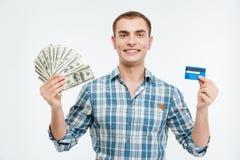 Χαμογελώντας ελκυστικά μετρητά εκμετάλλευσης νεαρών άνδρων και πιστωτική κάρτα Στοκ Φωτογραφίες