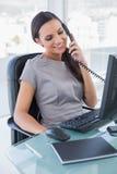 Χαμογελώντας ελκυστική επιχειρηματίας που απαντά στο τηλέφωνο Στοκ Εικόνες