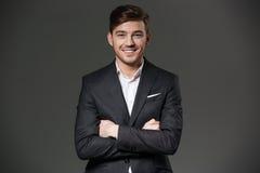 Χαμογελώντας ελκυστικός επιχειρηματίας στο μαύρο κοστούμι που στέκεται με τα χέρια που διπλώνονται Στοκ Εικόνα