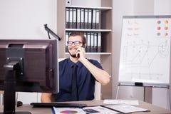 Χαμογελώντας ελκυστικός επιχειρηματίας στο μπλε πουκάμισο και δεσμός που μιλά επάνω Στοκ εικόνα με δικαίωμα ελεύθερης χρήσης