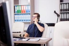 Χαμογελώντας ελκυστικός επιχειρηματίας στο μπλε πουκάμισο και δεσμός που μιλά επάνω Στοκ φωτογραφία με δικαίωμα ελεύθερης χρήσης