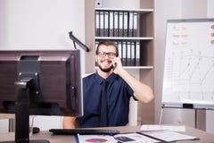 Χαμογελώντας ελκυστικός επιχειρηματίας στο μπλε πουκάμισο και δεσμός που μιλά επάνω Στοκ Εικόνες