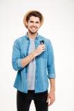 Χαμογελώντας ελκυστικός νεαρός άνδρας στο καπέλο που στέκεται και που κρατά τα γυαλιά ηλίου Στοκ εικόνες με δικαίωμα ελεύθερης χρήσης