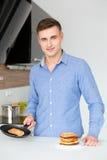 Χαμογελώντας ελκυστικό άτομο που μαγειρεύει και που κατασκευάζει τις τηγανίτες Στοκ φωτογραφία με δικαίωμα ελεύθερης χρήσης