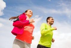 Χαμογελώντας ζεύγος με τα ακουστικά που τρέχουν υπαίθρια Στοκ φωτογραφία με δικαίωμα ελεύθερης χρήσης