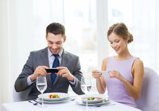 Χαμογελώντας ζεύγος με τα ορεκτικά και smartphones Στοκ Φωτογραφία