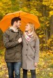Χαμογελώντας ζεύγος με την ομπρέλα στο πάρκο φθινοπώρου Στοκ εικόνα με δικαίωμα ελεύθερης χρήσης