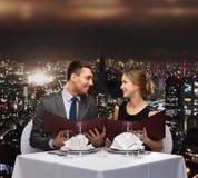 Χαμογελώντας ζεύγος με τις επιλογές στο εστιατόριο Στοκ εικόνα με δικαίωμα ελεύθερης χρήσης