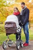 Χαμογελώντας ζεύγος με το καροτσάκι μωρών στο πάρκο φθινοπώρου Στοκ Εικόνα