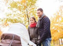 Χαμογελώντας ζεύγος με το καροτσάκι μωρών στο πάρκο φθινοπώρου Στοκ Εικόνες