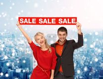 Χαμογελώντας ζεύγος με το κόκκινο σημάδι πώλησης Στοκ Εικόνες