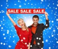 Χαμογελώντας ζεύγος με το κόκκινο σημάδι πώλησης Στοκ φωτογραφίες με δικαίωμα ελεύθερης χρήσης