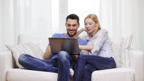 Χαμογελώντας ζεύγος με το φορητό προσωπικό υπολογιστή στο σπίτι απόθεμα βίντεο