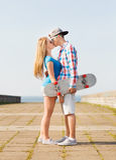 Χαμογελώντας ζεύγος με skateboard που φιλά υπαίθρια Στοκ εικόνα με δικαίωμα ελεύθερης χρήσης