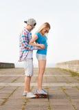 Χαμογελώντας ζεύγος με skateboard υπαίθρια Στοκ Φωτογραφίες