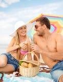 Χαμογελώντας ζεύγος που έχει το πικ-νίκ στην παραλία Στοκ Εικόνα