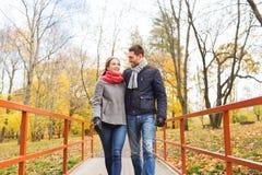 Χαμογελώντας ζεύγος που αγκαλιάζει στη γέφυρα στο πάρκο φθινοπώρου Στοκ εικόνες με δικαίωμα ελεύθερης χρήσης