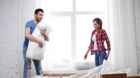 Χαμογελώντας ζεύγος που ανοίγει το μεγάλο κουτί από χαρτόνι με τον καναπέ απόθεμα βίντεο