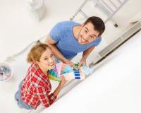 Χαμογελώντας ζεύγος που εξετάζει τα δείγματα χρώματος στο σπίτι Στοκ φωτογραφία με δικαίωμα ελεύθερης χρήσης