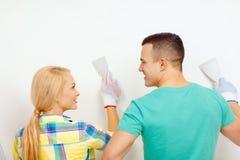 Χαμογελώντας ζεύγος που κάνει τις ανακαινίσεις στο σπίτι στοκ εικόνα